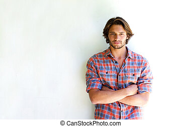 Serious young man with arms crossed on white background