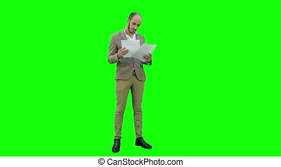 Serious young manager standing and reading documents on a Green Screen, Chroma Key.