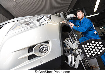 Serious young mechanic adjusting automobile wheel alignment