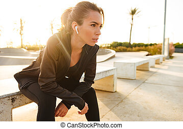 Serious young sports woman sitting outdoors listening music