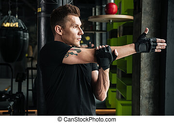 Serious young sportsman make stretching exercises in gym.