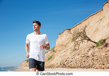 Serious young sportsman running on the beach - Serious young...
