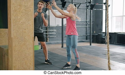 Serious young sportswoman is exercising in gym with personal instructor throwing ball and squatting busy with power exercise. Coach is speaking motivating girl.