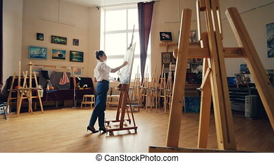 Serious young woman artist is working at picture painting...