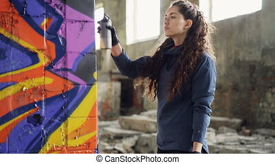 Serious young woman graffiti artist is painting on column in...