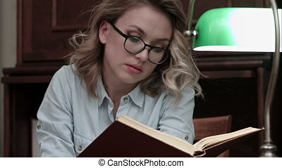 Serious young woman in glasses looking for informaton in the book