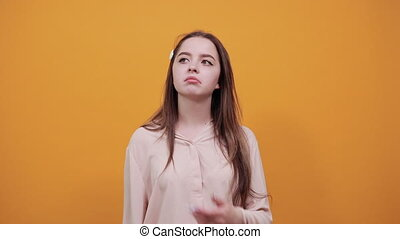 Serious young woman keeping finger on chin, thinking about issue wearing fashion pastel shirt isolated on orange background in studio. People sincere emotions, lifestyle concept.