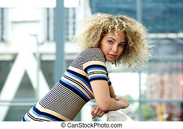 Serious young woman leaning on railing