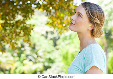 Serious young woman looking at leav - Side view of a serious...