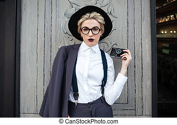 Serious young woman photographer with photo camera