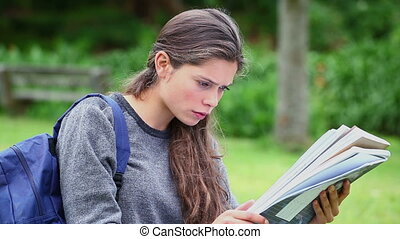 Serious young woman reading a document