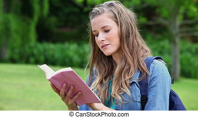 Serious young woman reading a novel in a park
