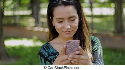 Serious young woman reading an sms on a mobile