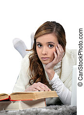 Serious young woman reading books
