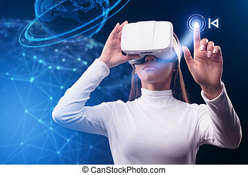 Serious young woman using virtual reality device