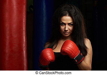 Serious young woman with boxing gloves