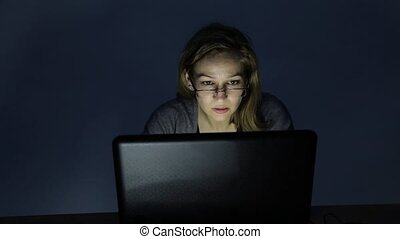 Serious young woman working on laptop in the dark room