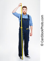 Serious young worker standing and measuring his growth with tape