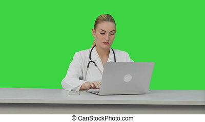Seriouse female doctor working on her laptop on a Green Screen, Chroma Key.