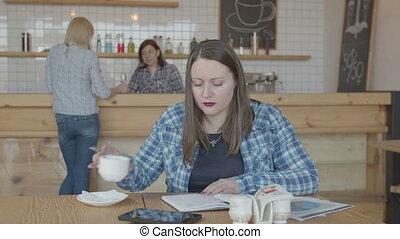 Seroius female freelancer working remotely in cafe -...