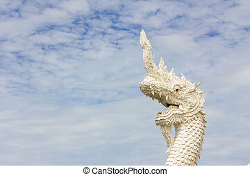 serpent king or king of naga statue in thai temple in background of cloudy sky