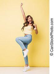 serrage, brun, 20s, femme, poings, réjouir, photo, sur, isolé, jaune, longueur cheveux, entiers, plaisir, long, fond, crier, content