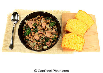 Served in black bowl New Years Day Traditional American South cooked meal, Chopped Ham and Collard Greens, Black-eyed Pea, Onion, white serviette, Slices Corn Bread Spoon over white background