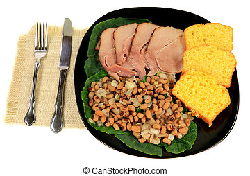 Served In black dish American South Traditional New Years Day meal, Slices Spiral-cut smoked Ham, Cooked Black-eyed Pee over Collard Greens, Cuts of Corn Bread, white serviette over white background
