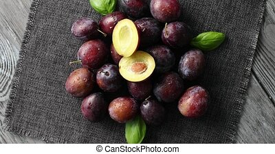 Served ripe plums on napkin - From above view of ripe shiny...