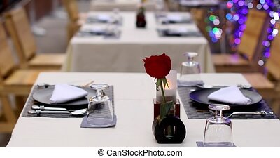 Served table with red rose in vase - Table set for dinner...