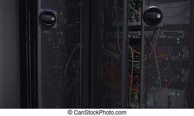 Server rack flashing led lights are in a modern data center are located behind an iron door with round openings
