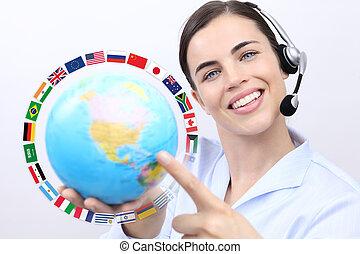 serviço freguês, operador, mulher, com, headset, sorrindo, segurando, globo, bandeiras internacionais, contactar-nos, conceito
