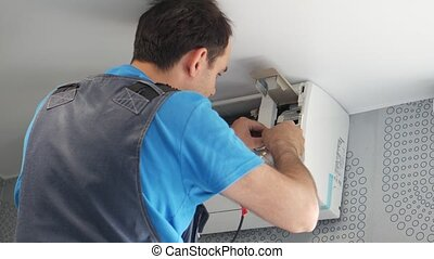 Service man installing air conditioner