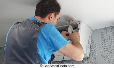 Service man installing air conditioner
