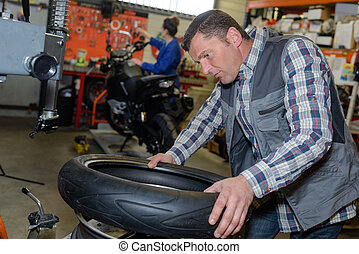 service mechanic with installer replace tyre on wheel in workshop