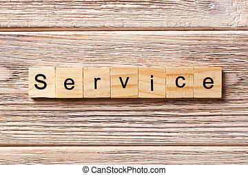 Service word written on wood block. Service text on table, concept