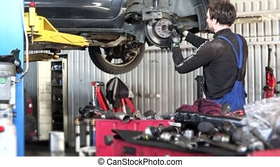 Service worker man change rusty car brake disk.