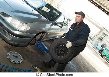 serviceman at tyre work - taking off tyre from car for...