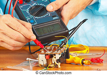 Serviceman checks electronic components of device with...
