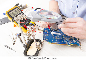 Serviceman checks PCB with a digital multimeter in the...