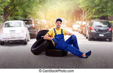 Serviceman in uniform sitting on a pile of tires, street...