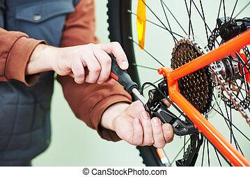 serviceman installing assembling or adjusting bicycle gear...