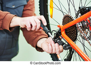 serviceman installing assembling or adjusting bicycle gear...