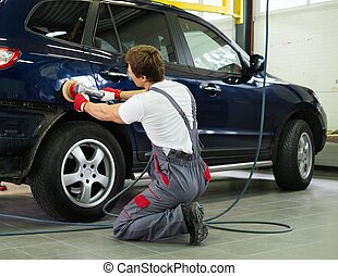 Serviceman polishing car body with machine  in a workshop