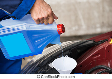 Serviceman Pouring Windshield Washer Fluid Into Car - ...
