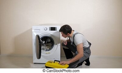 skilled serviceman in grey uniform with toolbox comes to check modern washing machine in light room