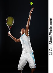 Serving a tennis ball - Young tennis player with racket...