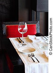 serving at table with white tablecloth and red chair in empty restaurant; one glass