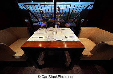 serving at table with white tablecloth and seats in empty restaurant at evening