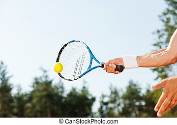 Serving ball. Close-up of male tennis player serving ball